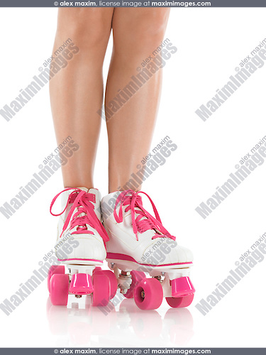 Closeup of legs of a young woman wearing white with pink classic roller girl derby skates isolated on white background