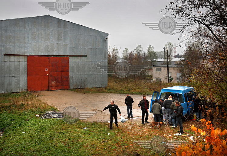 Heroin drug users queue by the Blue Bus. They are part of a group of dozens of addicts that come every day to receive clean needles and syringes from a team of social workers from a hospital in Vilnius who attempt to reduce the harm caused by addiction.