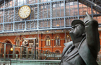 """John Betjeman (detail), larger-than-lifesize bronze statue, 2007, Martin Jennings, St Pancras International, with """"The Meeting Place"""", by Paul Day, 2007, and the famous St. Pancras Clock in the background, London, UK. Picture by Manuel Cohen"""