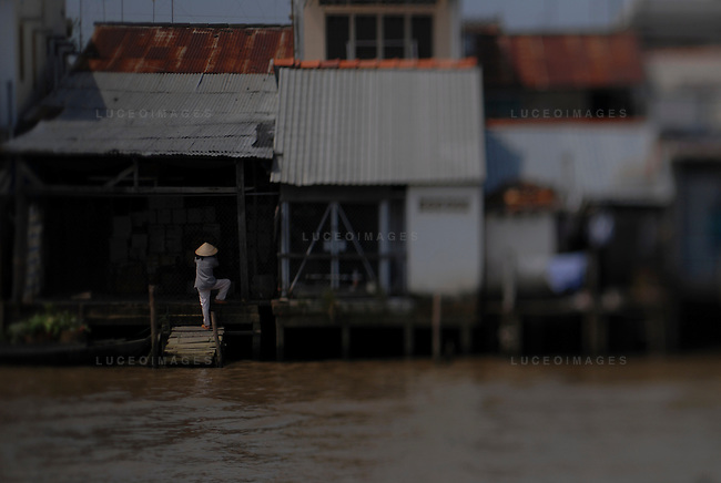 A Vietnamese woman goes about her daily life on the Mekong River in Vietnam.
