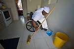 Jennifer Mhlanga suffered a spinal injury in a bus accident, and today uses a wheelchair to get around her home and neighborhood in Harare, Zimbabwe. Here she sweeps the floor in her kitchen. Mhlanga's wheelchair, which was carefully fitted to her individual needs, was provided by the Jairos Jiri Association with support from CBM-US.