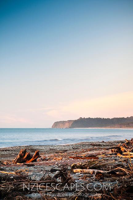 Driftwood ladden beach during setting sun at Bruce Bay - South Westland, West Coast, New Zealand
