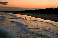 Several fisherman take advantage of a beautiful evening at sunset to surf fish off the beach of Myrtle Beach State park, South Carolina.