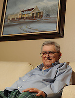 NWA Democrat-Gazette/ANDY SHUPE<br /> Al Witte sits Wednesday, Sept. 9, 2015, beneath a painting of the train depot in Fayetteville in his Fayetteville apartment. Witte worked as a law professor at the University of Arkansas for 59 years and served as president of the NCAA. Witte hired Bill Clinton, then still in law school, as a professor and has been an influence on a great many people.