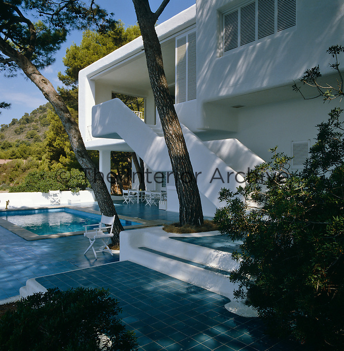 The blue-tiled swimming pool terrace reflects the bare whitewashed walls of this 1960s holiday home and the sinuous curves of the staircase