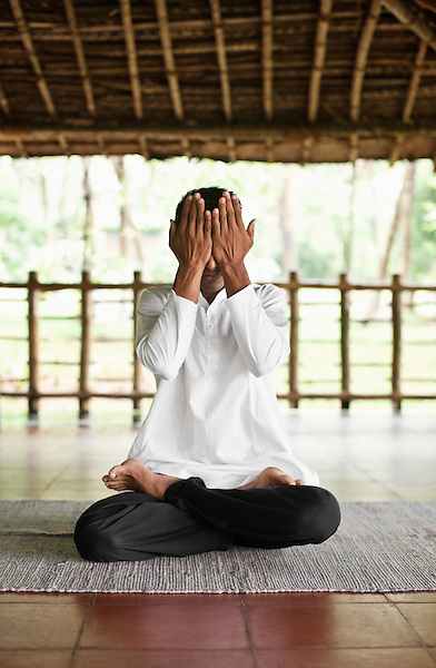 Man Practicing Yoga, Kairali Ayurvedic Health Resort, Palakkad, Kerala, India. A male yoga instructor practices yoga postures in an open-air yoga shala.