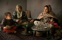 The Saharawi refugee camp  Smara..Sahrawi women with children preparing tea inside the tent.January 2008