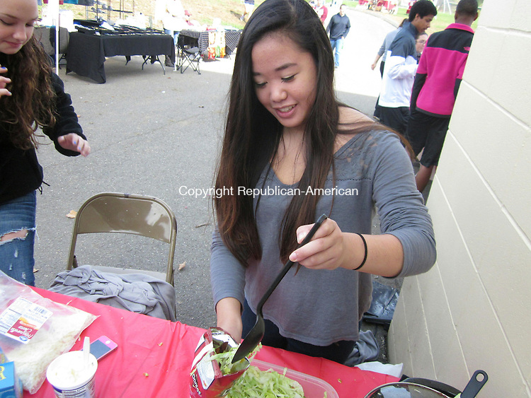 """TORRINGTON, CT- 19 October 2013- 101913BJ01-- Torrington High School freshman Andrea Sananikone scoops in some taco meat and shredded lettuce inside a Doritos bag as part of a fundraiser during a the T-Fest, Torrington High School Homecoming Fair. The freshmen class sold the """"tacos in a bag"""" for $3 as a fundraiser. Other classes and student groups sold food and held different activites during the event. Bruno Matarazzo Jr. Republican-American"""