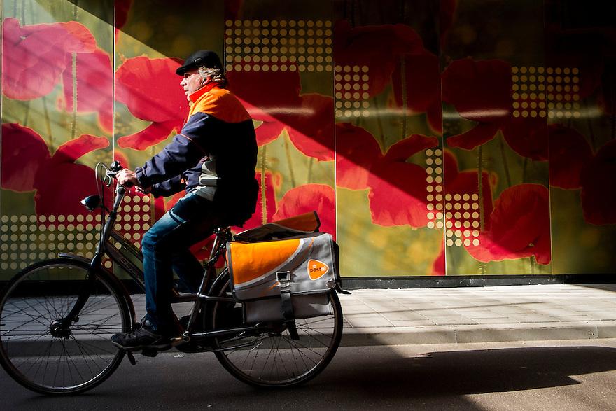 Nederland, Utrecht, 5 maart 2014<br /> Postbezorger van PostNL fiets door een tunneltje met mooie wandbekleding.<br />  <br /> Foto(c): Michiel Wijnbergh