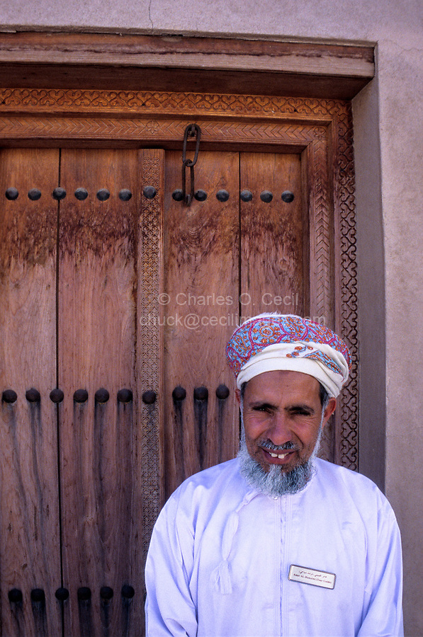 Jabrin, Oman.  Tour Guide at the Jabrin Fort, wearing an Msarr, the traditional Omani headdress, and white dishdasha.