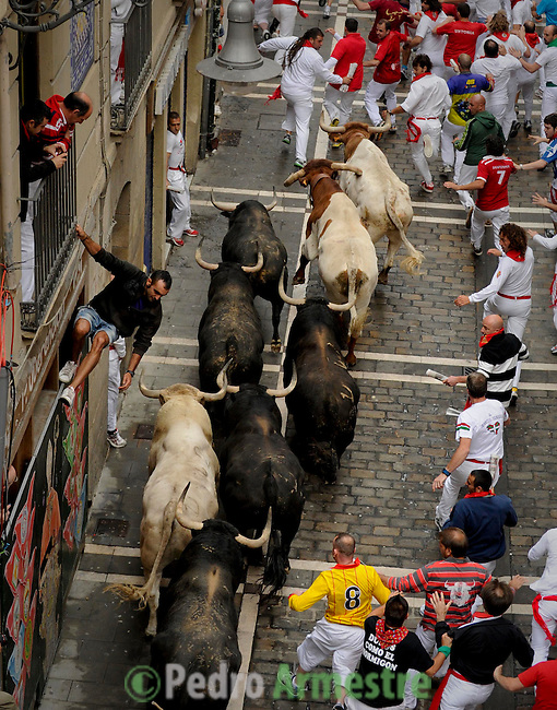 Participants run in front of Fuente Ymbro's bulls during the fifth San Fermin Festival bull run, on July 11, 2012, in Pamplona, northern Spain. The festival is a symbol of Spanish culture that attracts thousands of tourists to watch the bull runs despite heavy condemnation from animal rights groups. (c) Pedro ARMESTRE. (c) Pedro ARMESTRE