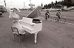 Stuffed rabbit doll sitting and playing a piano along busy highway with onlookers riding their bikes