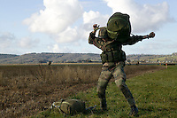 A member of the French Foreign Legion loads his equipment onto his back after jumping over the airport of Tarbes, France, during a full scale multi-force exercise, 11 December 2007.