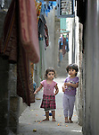 Two girls in a narrow street in the Al-Shalti refugee camp in Gaza. Residents of the Palestinian territory are still reeling from the death and destruction of the 2014 war with Israel, and the continuing siege of the seaside territory by the Israeli military.