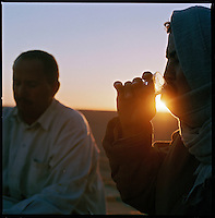 Sahara desert, Libya-Chad, November/December 2004..Every week, a convoy of 40 privately owned Libyan trucks loaded by the WFP with about 1000 metric tons of western food aid cross 2500 km of deep desert across Libya and Chad to reach more than 200 000 refugees from Darfur in camps near the Sudanese border. Moussa and Naher make tea in the cold desert evening.