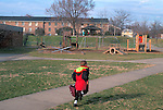 A child runs toward a playground and apartment buildings in Alexandria, VA