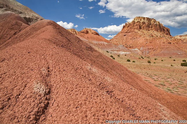 A sandstone tower looms in the distance behind a ridge of colored earth at Kitchen Mesa at Ghost Ranch, near Abiquiu, New Mexico.
