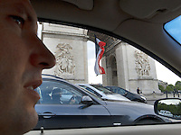 France. Paris. Arc de Triomphe. Toni Srdanovic drives his car on the Place Charles de Gaulle. Policemen and french flag. The Place Charles de Gaulle, historically known as the Place de l'&Eacute;toile, is a large road junction and the meeting point of twelve straight avenues (hence its historic name, which translates as &quot;Square of the Star&quot;). It was renamed in 1970 following the death of General and President Charles de Gaulle. It is still often referred to by its original name. Model released. 18.06.10 &copy; 2010  Didier Ruef..