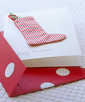 A handmade Christmas card is decorated with a checked stocking containing a scented cedar sprig