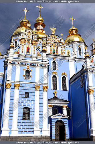 Saint Michael's sky-blue beautiful christian cathedral with golden domes in Kiev Ukraine Eastern Europe under dramatic cloudy sky Vertical orientation
