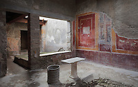 Atrium of the Casa di Fabio Amandio, or House of Fabius Amandus, with frescoes in the Fourth Style of Roman wall painting, 60-79 AD, and an iron water drum, Pompeii, Italy. Pompeii is a Roman town which was destroyed and buried under 4-6 m of volcanic ash in the eruption of Mount Vesuvius in 79 AD. Buildings and artefacts were preserved in the ash and have been excavated and restored. Pompeii is listed as a UNESCO World Heritage Site. Picture by Manuel Cohen