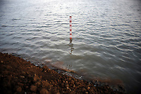Depth marker in the mud lake showing 5.8 metres. Since May 2006, more than 10,000 people in the Porong subdistrict of Sidoarjo have been displaced by hot mud flowing from a natural gas well that was being drilled by the oil company Lapindo Brantas. The torrent of mud - up to 125,000 cubic metres per day - continued to flow three years later.