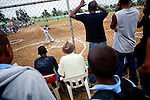Local townspeople watch players perform in a showcase for Major League Baseball scouts on Friday, February 26, 2010 in San Antonio de Guerra, Dominican Republic.