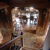 An elevated view from the top of a staircase looking down to a wood panelled hallway entrance with a tiled floor. A dining area is seen through an archway.