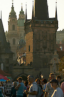 Czeck Republic - Prague, tourists and passersby on the Charles bridge in the late afternoon light. Behind is the bridge tower, the buildings along Mostecká, and the St. Nicholas Church in Malá Strana.