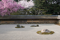 The Ryoan-Ji Temple garden features 15 irregularly shaped rocks grouped in five clusters of varying sizes arranged on a surface of white gravel