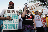 """Phoenix, Arizona. June 25, 2012 - Puente Arizona activists Orlando Arenas (left) and Erika Ovalle (with bullhorn) lead demonstrators with protest's chants like """"Arrest Arpaio, not the people."""" Arenas was arrested by Sheriff Arpaio's deputies in 2009 for protesting at a county jail.  Immigrant rights groups protested the United States Supreme Court ruling on Arizona law for upholding SB 1070's provision that will allow police to demand papers if there's reasonable suspicion that a person may be illegally in the country. Photo by Eduardo Barraza © 2012"""