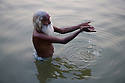 """Indian holy man, """"Sadhu"""" bathing and praying in Ganges River;  Varanasi has been a cultural and religious center in northern India for several thousand years, Varanasi, Uttar Pradesh, India --- Model Released"""
