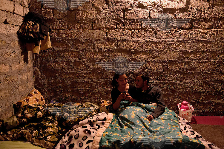Aida talks to her husband Rashid before they go to sleep at their temporary house near Dohuk. <br /> Aida, a 21 year old mother of two small children, was captured with her one year old son and two year old daughter by Islamic State (IS) fighters in Sinjar when IS invaded the city in August 2014. During her two months in IS captivity she was moved around frequently to various towns in the region. They were often beaten and one day an IS fighter pointed a gun to her daughter's face. 'One day I stole a mobile phone at the IS house and called my family.... My husband asked one of his Muslim friends to help him rescue me.... When everything was ready I ran away from the IS house and was rescued by my husband's friend one km from where I was captured. My family paid $ 4,000 to two people who picked up myself and my children and drove us to a safer area. We lost everything.' Aida is now living with her parents in a small house they are renting near Dohuk. Her mother in law is still in IS captivity. Her father was killed in front of her by IS fighters.