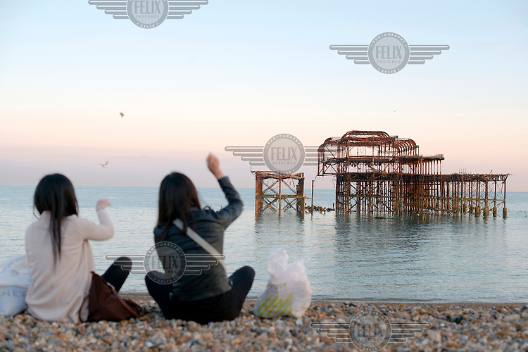 Two Chinese students throw stones into the sea at  the beach near the burned out West Pier in the Sussex town of Brighton.