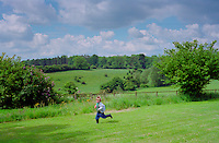 A four year old boy running across a field in Wiltshire, England