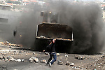 A Palestinian protester throws stones at an Israeli bulldozer during clashes following a protest against the expropriation of Palestinian land by Israel on March 31, 2013 in the village of Kfar Qaddum, near the occupied West Bank city of Nablus. Photo by Issam Rimawi