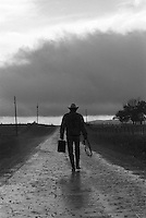 Cowboy carrying a suitcase and lasso walking down a wet dirt road during a storm