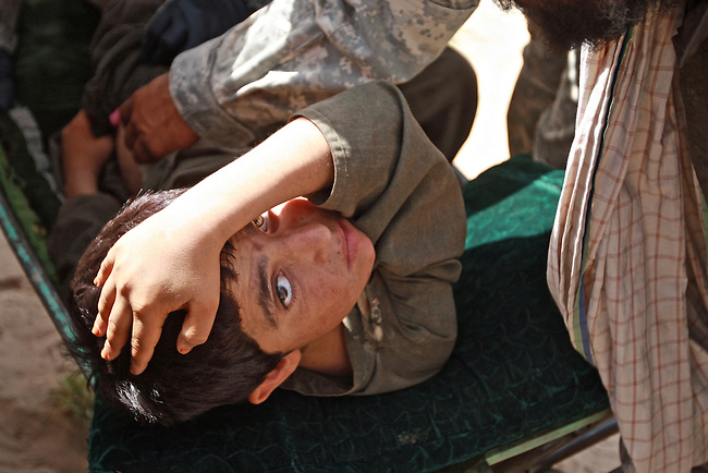 A U.S. medic treats an Afghan boy who had been shot in the hip two months earlier when he was caught in a crossfire between U.S. soldiers and Taliban fighters in the village of Osman Kheyl, in Maiwand district, Kandahar province, Afghanistan. Aug. 7, 2008. DREW BROWN/STARS AND STRIPES