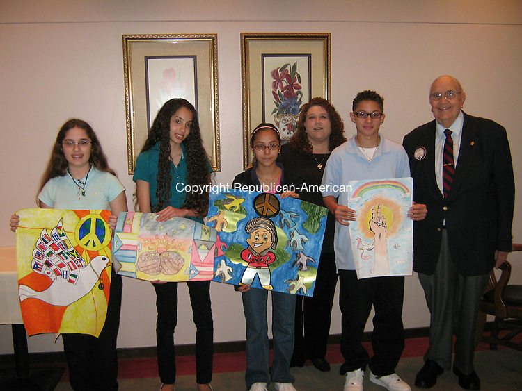 WATERBURY, CT - 7 May 2009 - 050709AL01 - Middle schoolers who won a peace poster contest sponsored by the Waterbury chapter of Lions Club International hold their posters during a ceremony at the Waterbury Club Thursday. The winners, from left, are Renee Manelli, 12, of West Side Middle School; Shanttelle Pacheco, 15, of Wallace Middle School; Marjorie Inga, 12, of North End Middle School and Carlos Velazquez, 13, of Waterbury Arts Magnet School. In the background are Lisa Martin, president of the Lions Club, and Michael Granatuk, chairman of the peace poster contest.