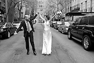 Exuberant shot of bride and groom standing in the street holding arms up in the air.