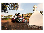 JOURNEYS AND MAPS : Two Harley riders take a break near a village cross near the church to find their way and their location on the India map on their journey in a village in Goa. Photograph &copy; Santosh Verma