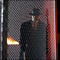 Black man in coat standing behind chain link fence