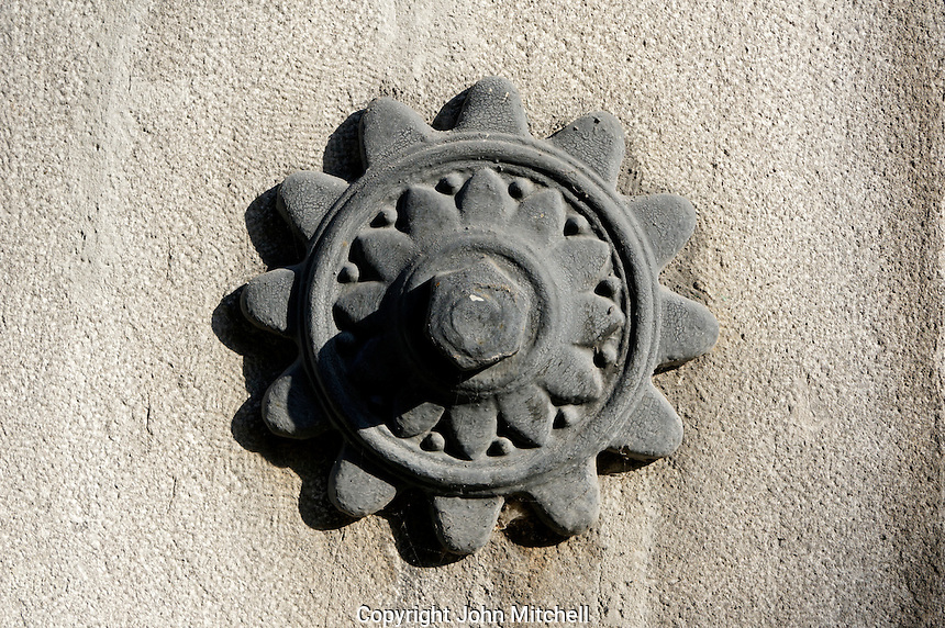 Circular iron decoration on the wall of  a historical building in Old Montreal, Quebec, Canada