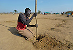 Amon Akuel Aler digs holes where she hopes to insert poles to begin the construction of a shelter in the internally displaced persons camp in Turalei, South Sudan. Families started arriving here shortly after fighting broke out in December 2013, and new families continued to arrive in March 2014 as fighting continued. Many are living in the open and under trees. The ACT Alliance is providing the displaced families and the host communities affected by their presence with a variety of support, including new wells. This woman has not seen her husband since the fighting began, and was separated from two of her five children as they fled Bentieu. She has not located them yet.
