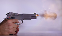 A .45 caliber handgun firing a bullet.  This image freezes the motion by using a high speed flash with a duration of   1/2,000,000th of a second.  The sparks are from gunpowder that was still burring as it left the barrel behind the bullet.