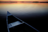 Evening light reflects warm rays of the setting sun on a canoe on the still waters of the St. Marys River. <br /> The St Marys River divides Florida and Georgia, flowing out of the Okefenokee Swamp to the Atlantic Ocean.