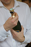 A man peels the foil from the top of a champagne bottle, in preparation for popping the cork