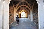 student walking thru duke archway on west campus