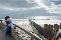 Lovers at the Mexican American border. Border fence at Playas de Tijuana, Tijuana, Baja California Norte, Mexico