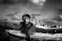 One of the new generation of surfers, Momen Abo A'ase 13, battles with the sea as he practises surfing, Gaza City, in the Gaza Strip.